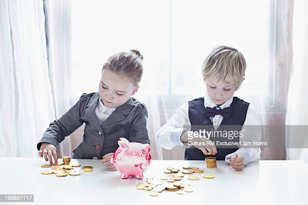 Children in suits counting gold coins