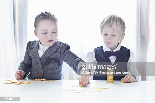 Children in suits counting gold coins : Stock Photo