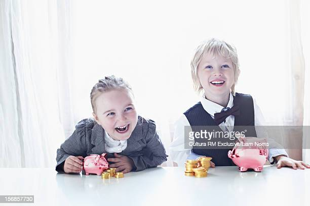 Children in suits with piggy banks