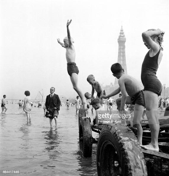 Children in swimming costumes jump into the sea from a boat trailer while adults paddle sedately Blackpool c1946c1955 Blackpool Tower provides a...