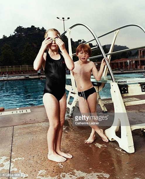 Children (6-8) in swimsuits standing next to diving board