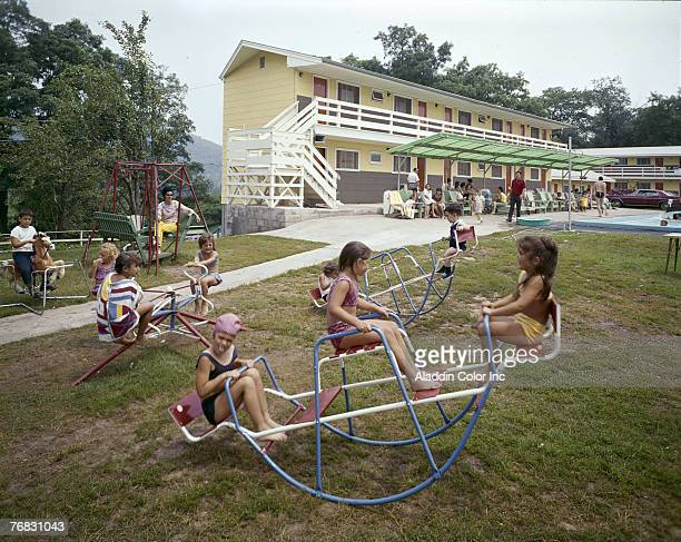 Children in swimwear play on several wireframe seesaws on the grass at the Jolly House Motel Resort in the Catskills New York 1960s A girl in a...
