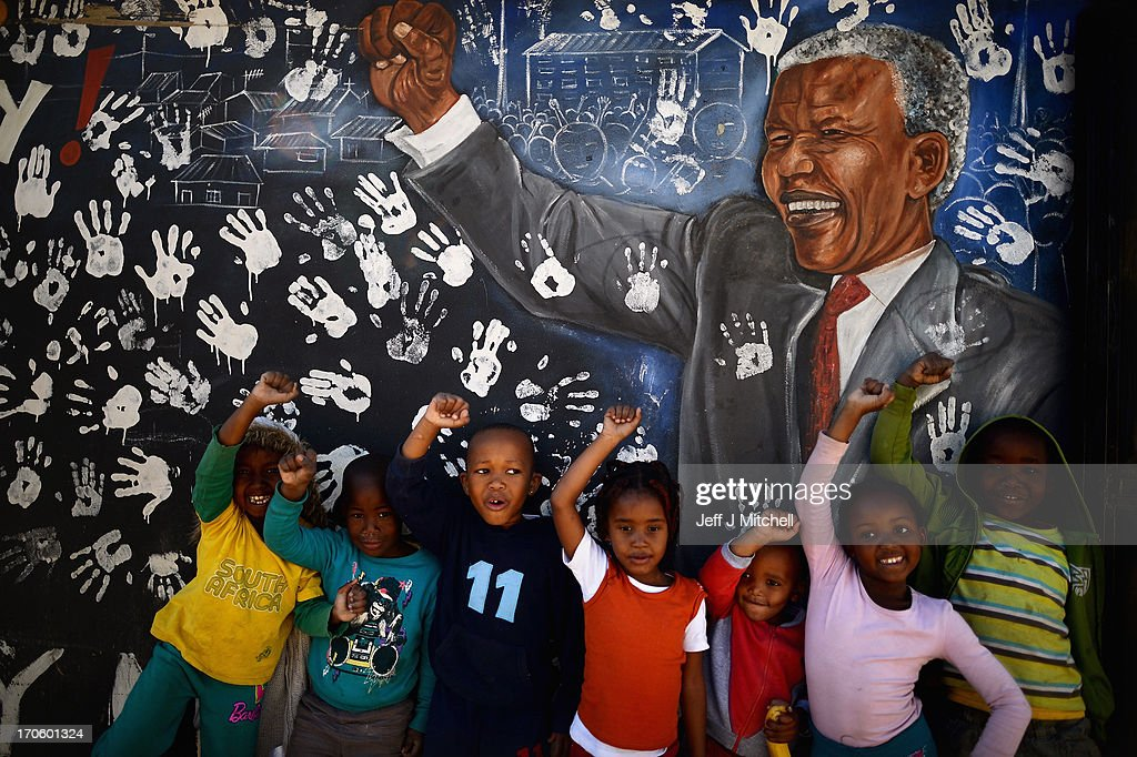 Children in the Alexandra Township stand next to a mural of Nelson Mandela on June 15,2013 in Johannesburg, South Africa. The former South African President and leader of the anti-apartheid movement is spending a seventh night in hospital and is reported to be responding better to treatment for a recurring lung infection.