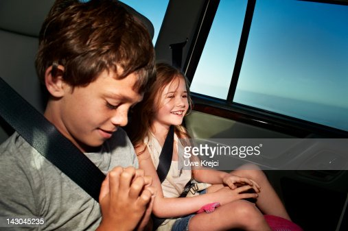 Children (5 - 8) in the back seat of car, smiling