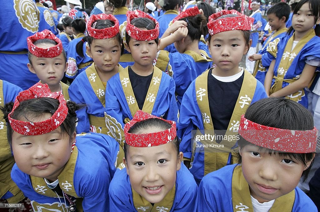 Children in traditional dress stand on the river bank as wood is pulled along the Isuzu River to the Inner Shrine of Japan's biggest shrine ?Ise Jingu? during the 62nd Okihiki-Gyoji ceremony on July 23, 2006 in Ise, Mie Prefecture, Japan. The Okihiki-Gyoji ceremony is conducted every 20 years for the last 1300 years and involves the shrines of Ise Jingu being moved and reconstructed and is called the Sengu, it is believed that by performing the Sengu the Japanese people will have their blessings renewed.