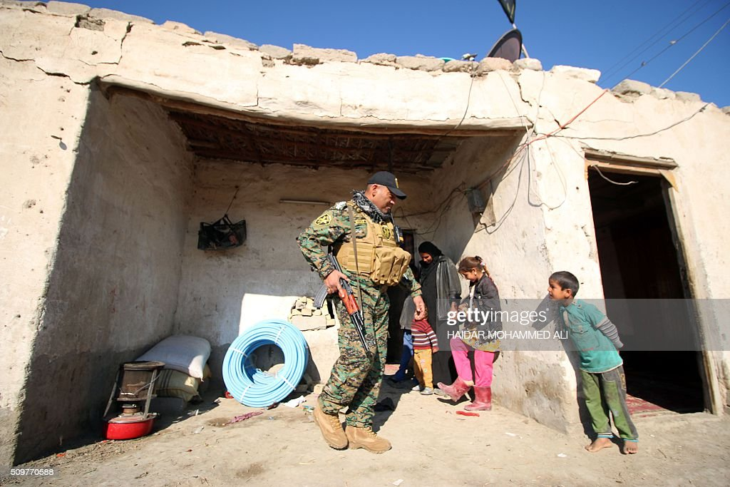 Children interact with a member of the Iraqi security forces outside their home in the Nahr al-Ezz area, 150km North of Basra, on February 12, 2016 during a security operation. Operations by the security forces, including the intelligence services, are regular in the area in an attempt to contain and disarm feuding local gangs and tribes. / AFP / HAIDAR MOHAMMED ALI