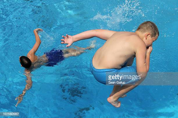 Children jump from a diving board at a public pool on July 1 2010 in Kleinmachnow near Berlin Germany Temperatures are predicted to continue to climb...