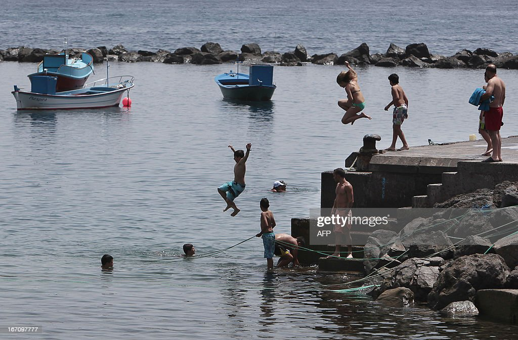 Children jump into the sea on April 20, 2013 on the Spanish Canary island of Tenerife, where temperatures are soaring due to the Sirocco, a Mediterranean wind coming from the Sahara.