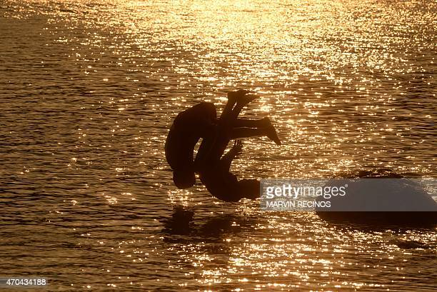 Children jump into the waters of Lake Suchitlan at sunset in Suchitoto 47 km east of San Salvador El Salvador on April 19 2015 AFP PHOTO/ Marvin...