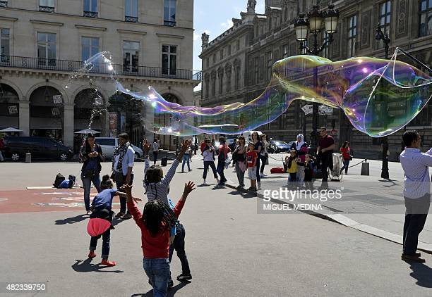 Children jump to burst a giant soap bubble in the 'Place du Palais Royal' in Paris on July 2015 AFP PHOTO/MIGUEL MEDINA