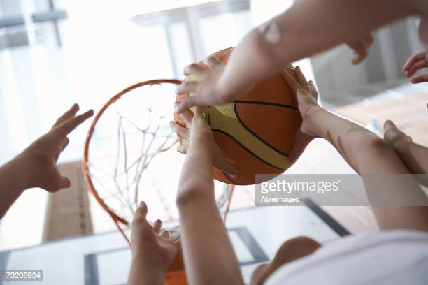 Children (9-12) jumping for basketball, close up of hands