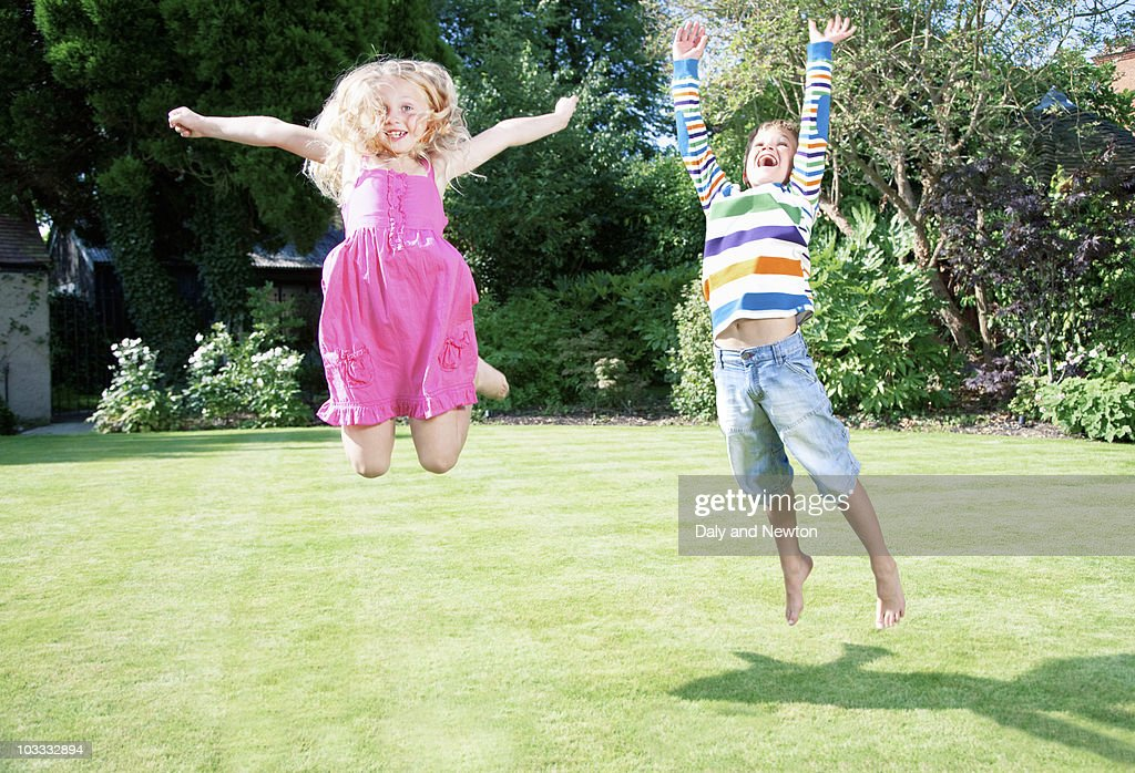 Children jumping in backyard : Stock Photo
