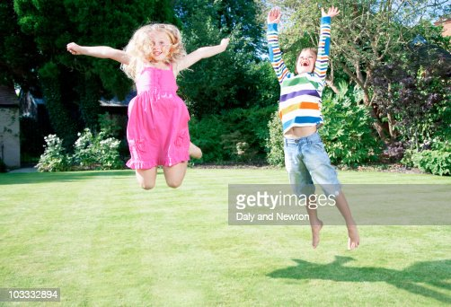 Children jumping in backyard : Stock Photo