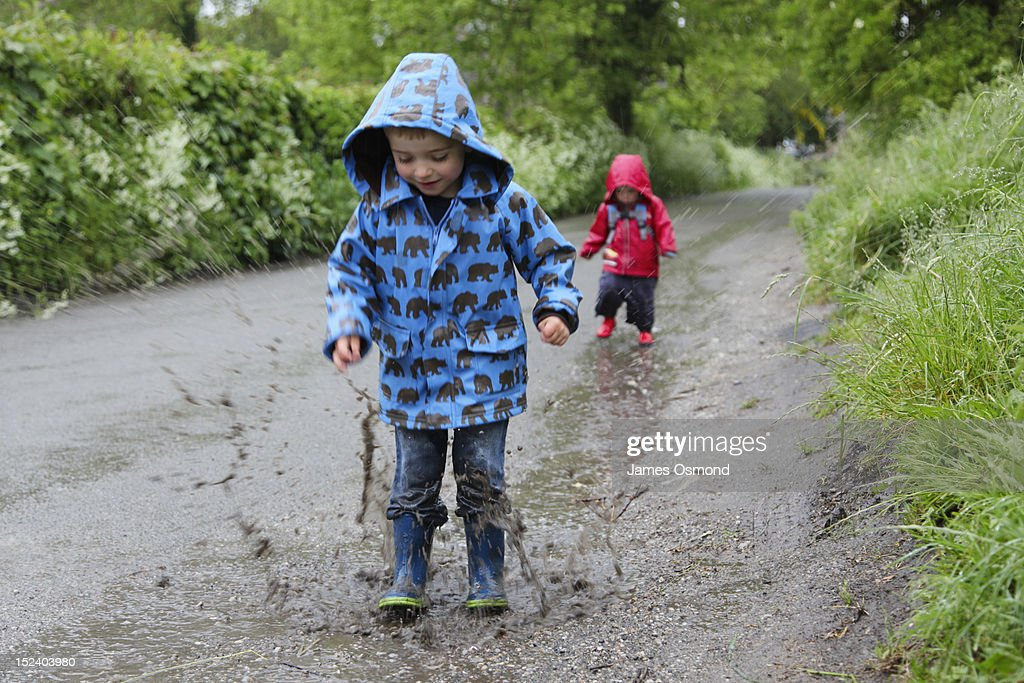 Children jumping in puddles. : Stock Photo