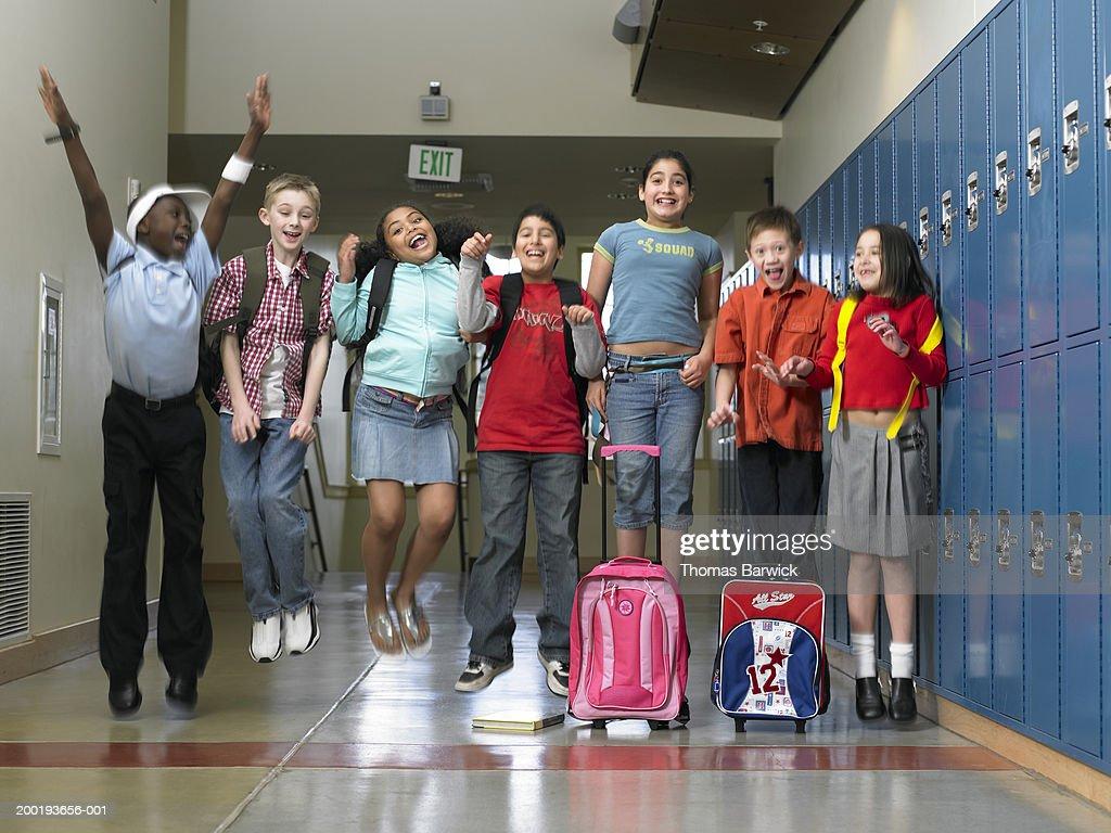 Children (8-10) jumping in school hallway (blurred motion) : Stock Photo