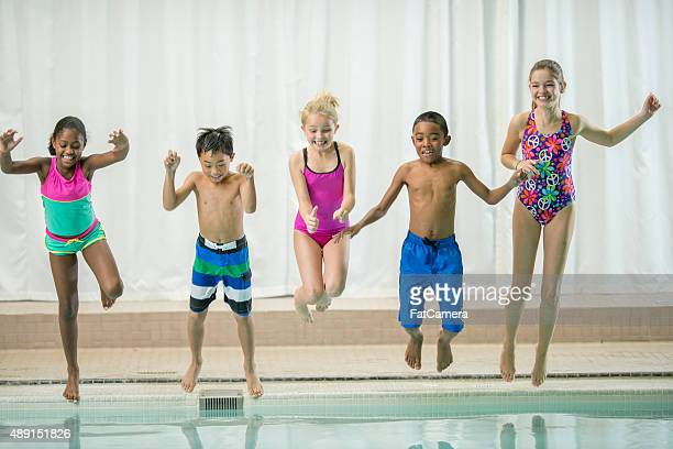 Enfants de sauter dans la piscine ensemble