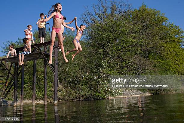 Children jumping into lake together
