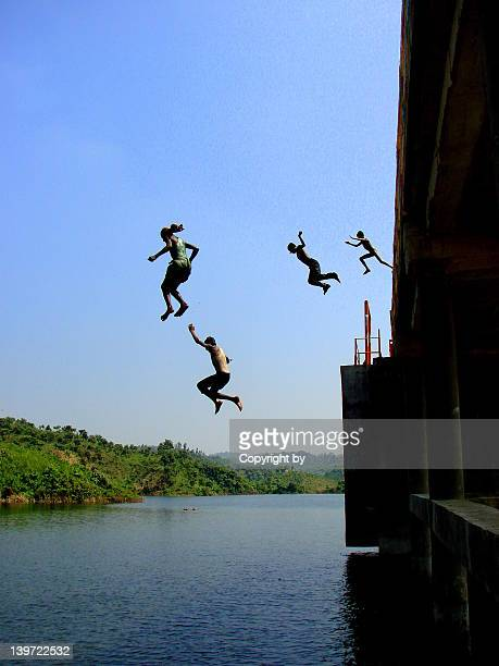 Children jumping into river from bridge