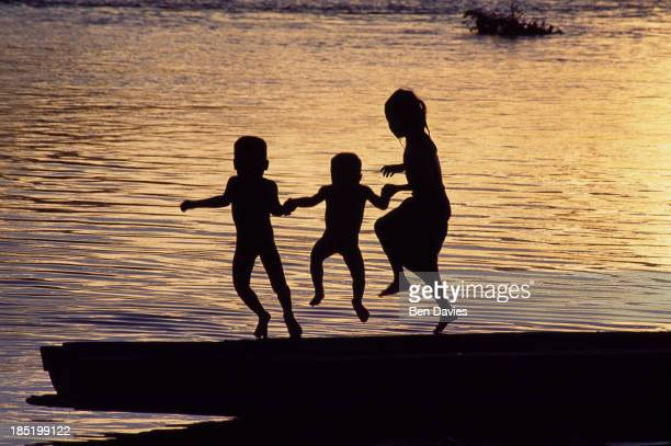 Children jumping into the Mekong River in Southern Laos at sunset The Mekong is one of the 12 great rivers of the world It symbolically links the...