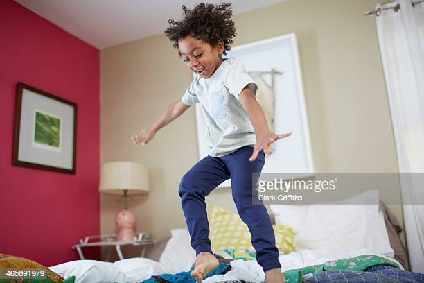Children jumping on bed