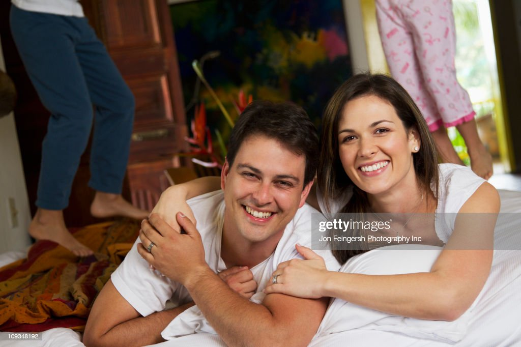 Children jumping on bed while parents smile : Stock Photo