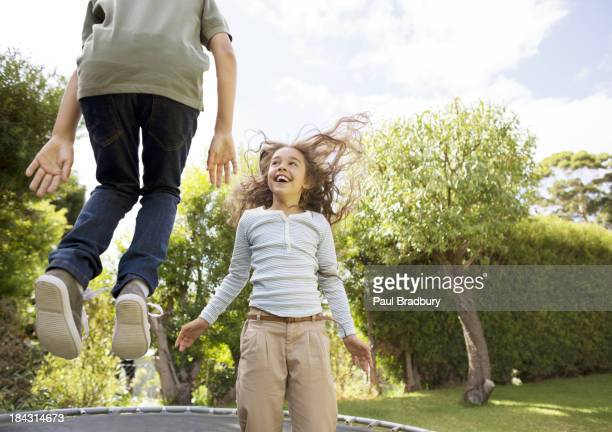 Children jumping on trampoline in backyard