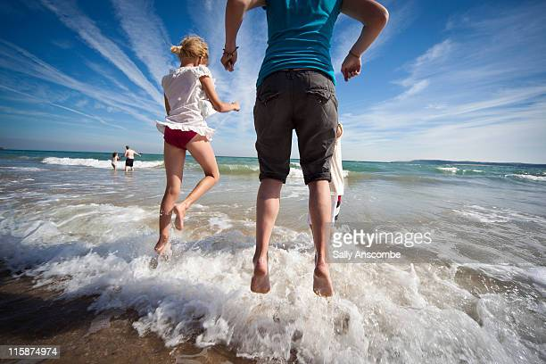 Children jumping over waves