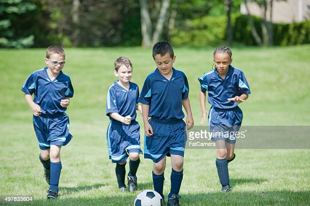 Children Kicking a Soccer Ball up the Field