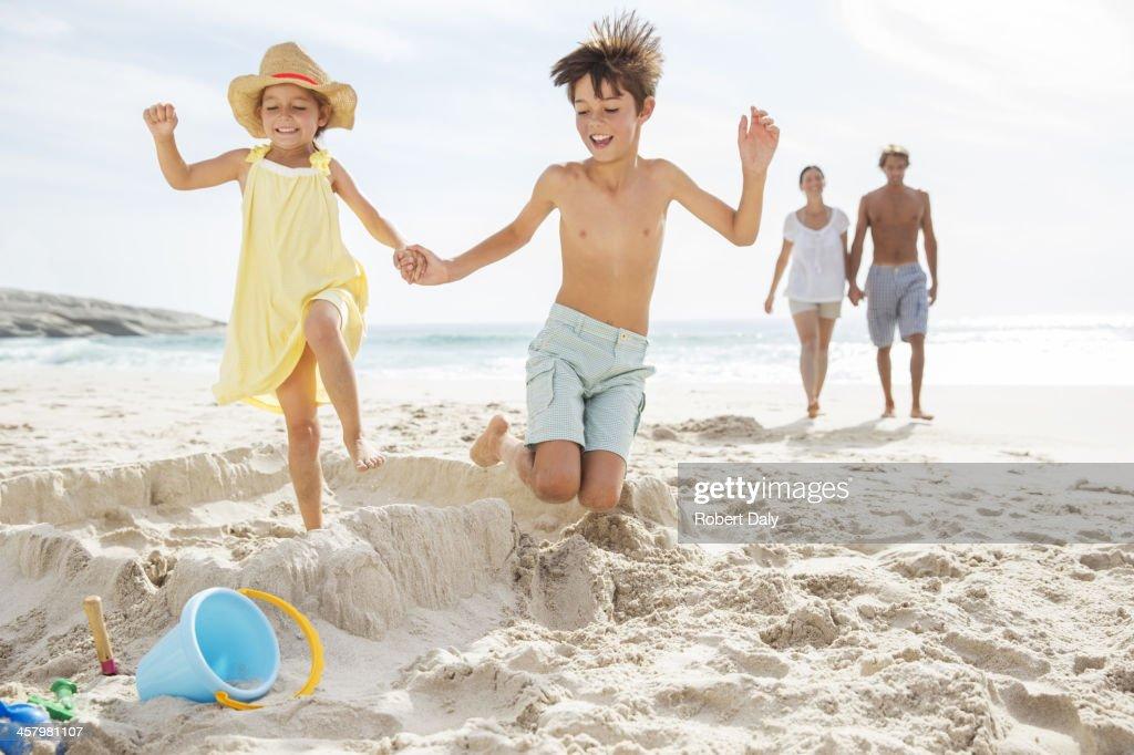 Children kicking down sandcastle on beach : Stock Photo