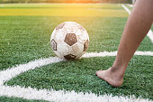 children kicking football on the sports field