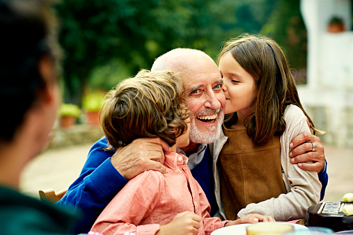 Children kissing grandfather at yard