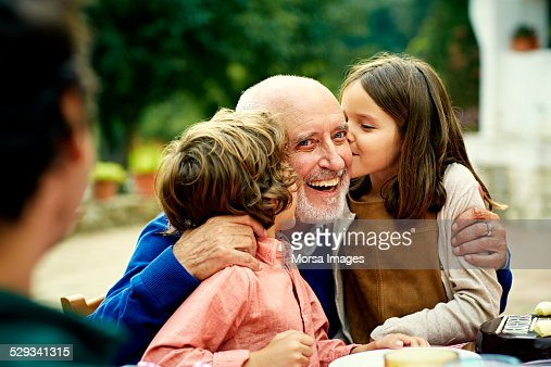 Children kissing grandfather at yard