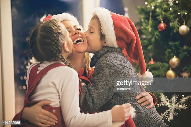 Children kissing mother on Christmas