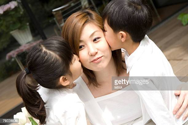 Children kissing to mother