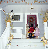 Children (2-8) knocking on door, trick-or-treating, rear view