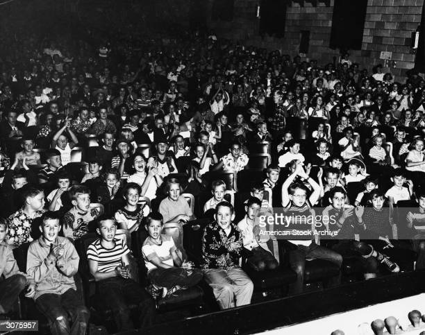 Children laugh clap and cheer while seated in the audience of a movie theater 1960s
