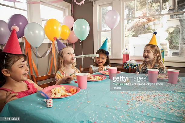 Children laughing at girl blowing party blower