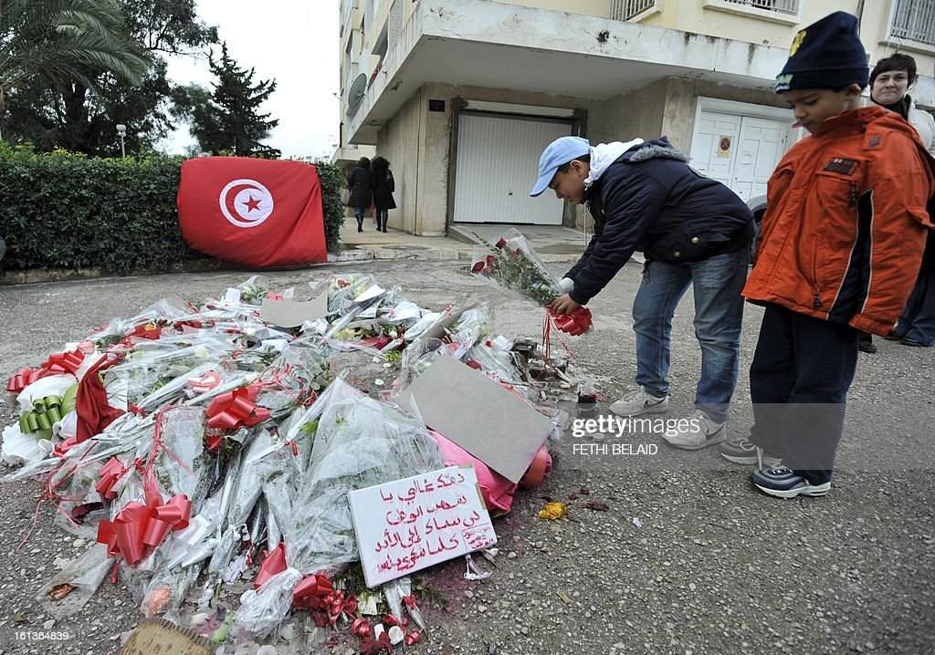 Children lay flowers at the spot where opposition leader Chokri Belaid was guned down on February 10, 2013, in the capital Tunis. Tunisian Prime Minister Hamadi Jebali's gamble on forming a new government in defiance of his own Islamist party after the assassination of Belaid has left Tunisia in political limbo. AFP PHOTO / FETHI BELAID