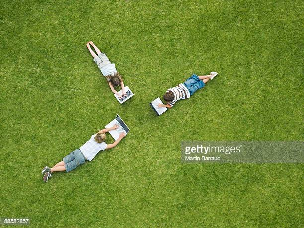 Children laying in grass typing on laptops