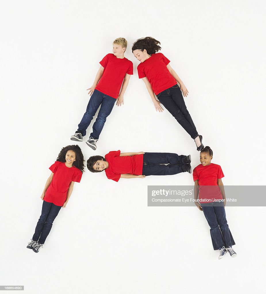 Children laying in letter 'A' formation : Stock Photo