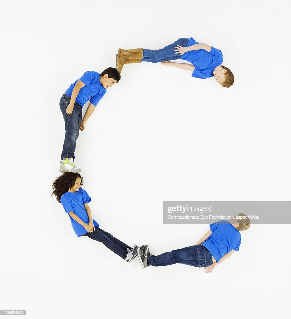 Children laying in letter 'C' formation : Stock Photo