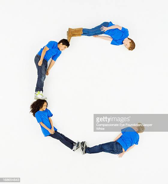 Children laying in letter 'C' formation