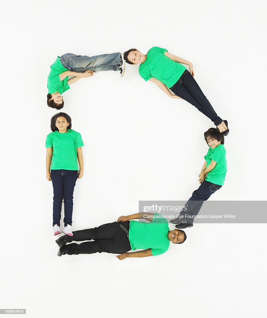 Children laying in letter 'D' formation : Stock Photo