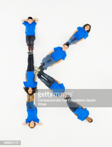 Children laying in letter 'K' formation : Stock Photo
