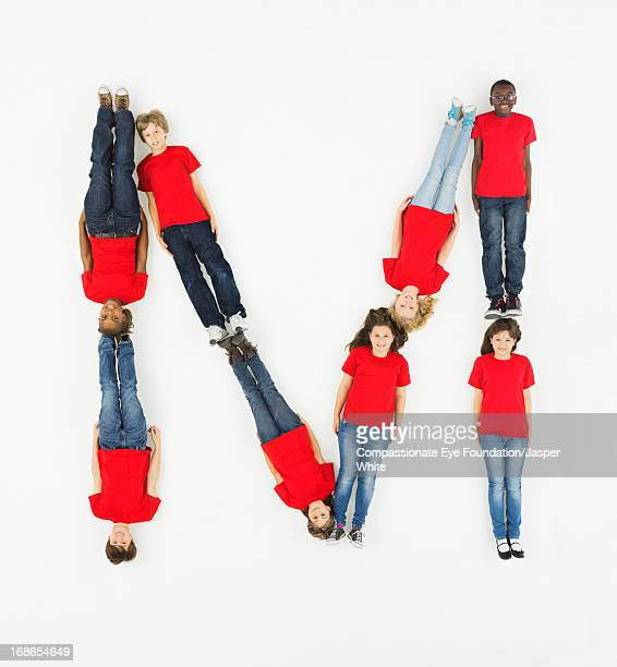 Children laying in letter 'M' formation