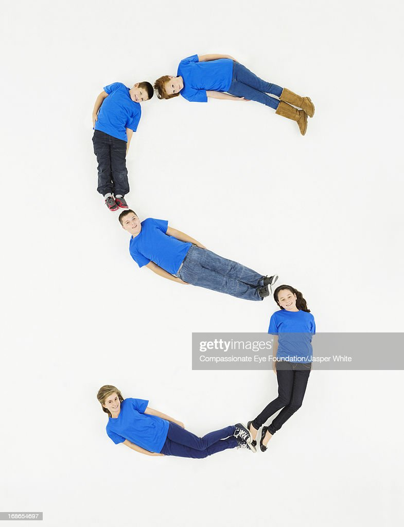 Children laying in letter 'S' formation : Stock Photo