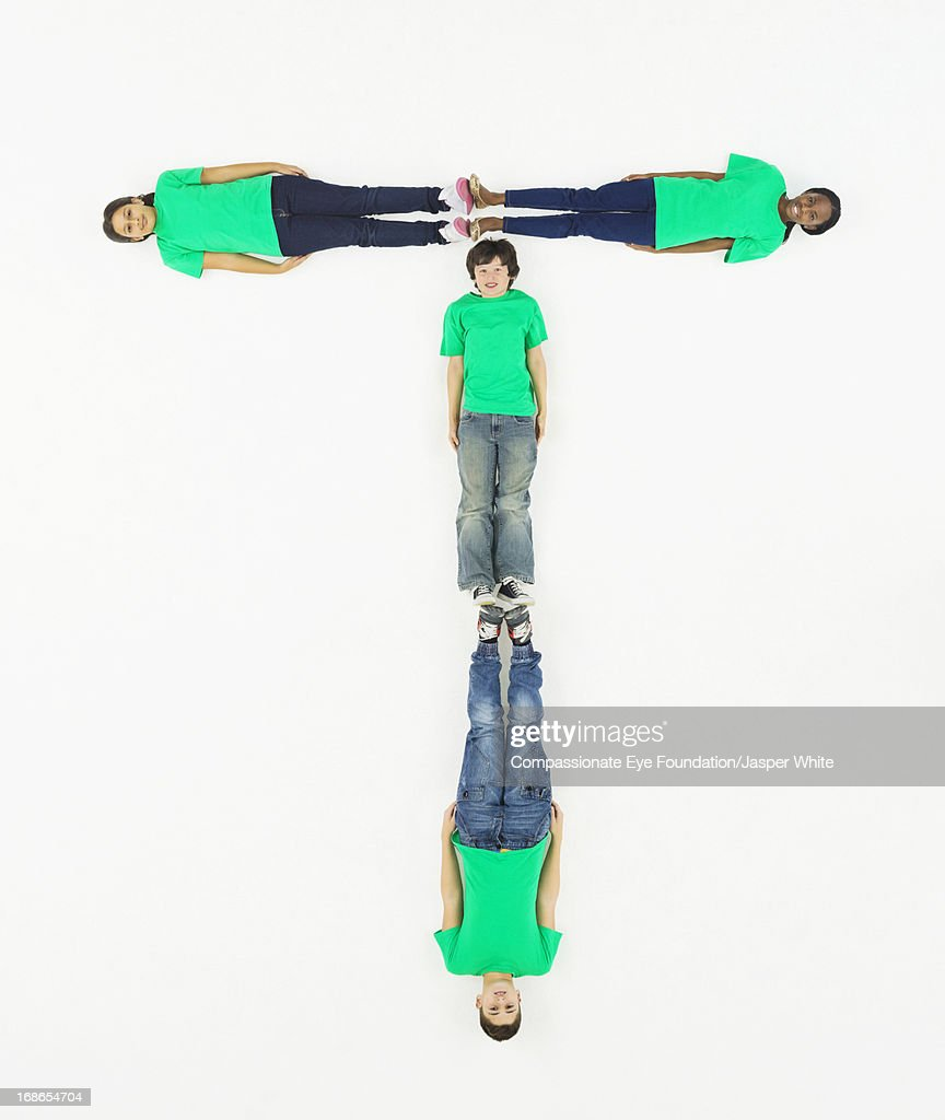 Children laying in letter 'T' formation : Stock Photo