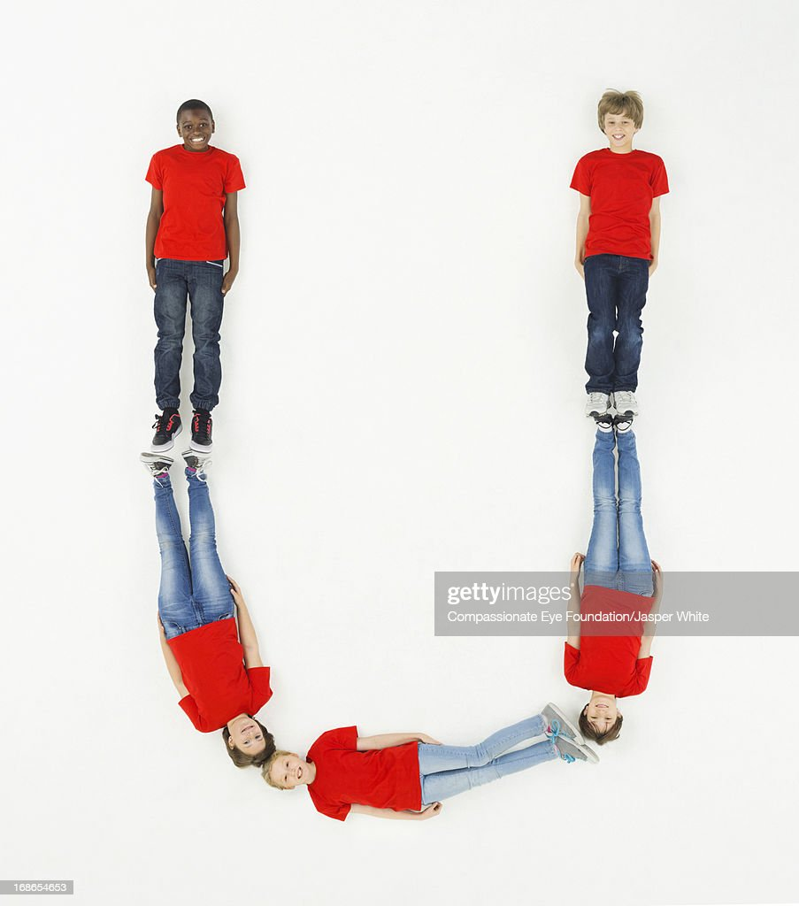 Children laying in letter 'U' formation : Stock Photo
