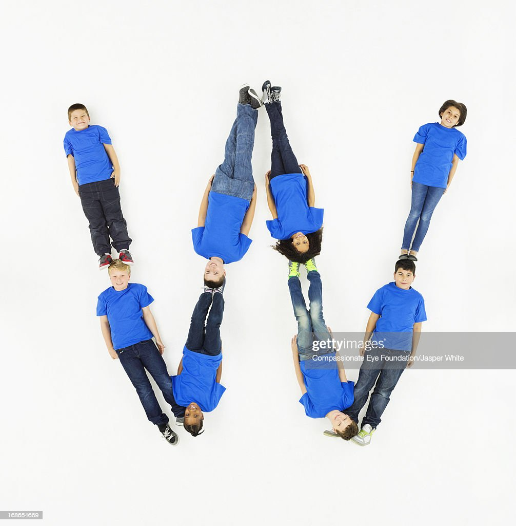 Children laying in letter 'W' formation : Stock Photo