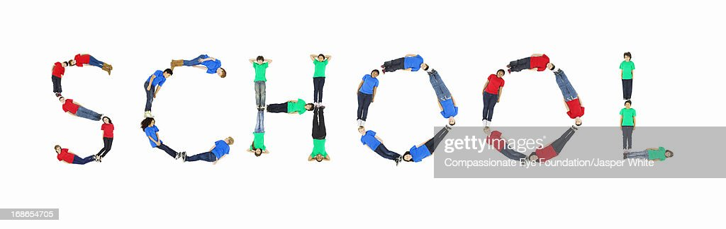 Children laying in 'SCHOOL' formation : Stock Photo